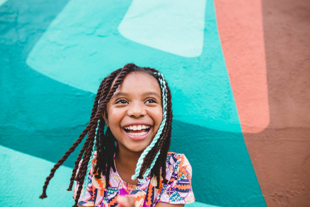 young girl smiles in front of bright mural wall south Philadelphia Lucy Baber Family Photographer