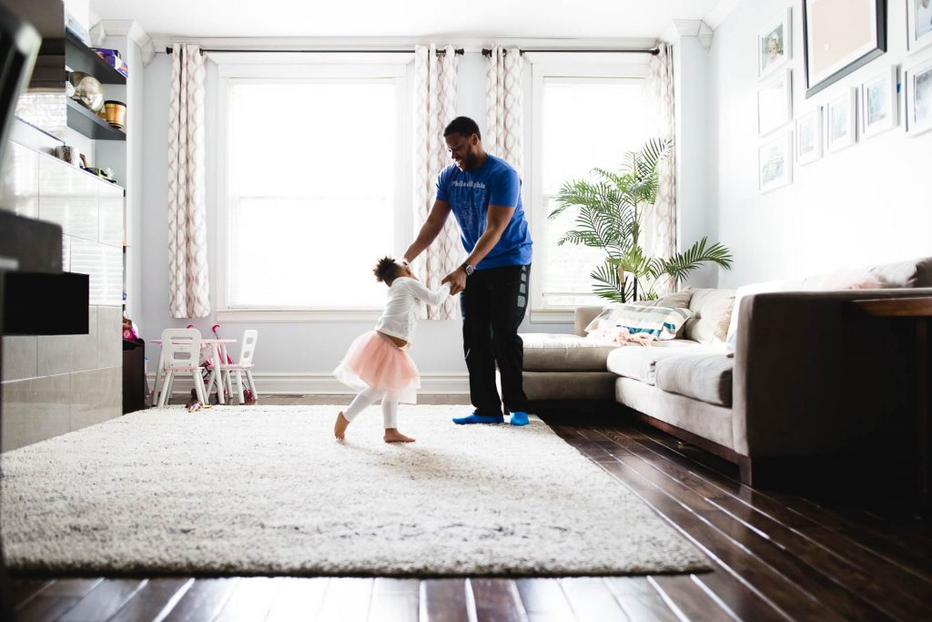 father dances with toddler daughter in tutu in living room at home Northwest Philadelphia Lucy Baber Photography