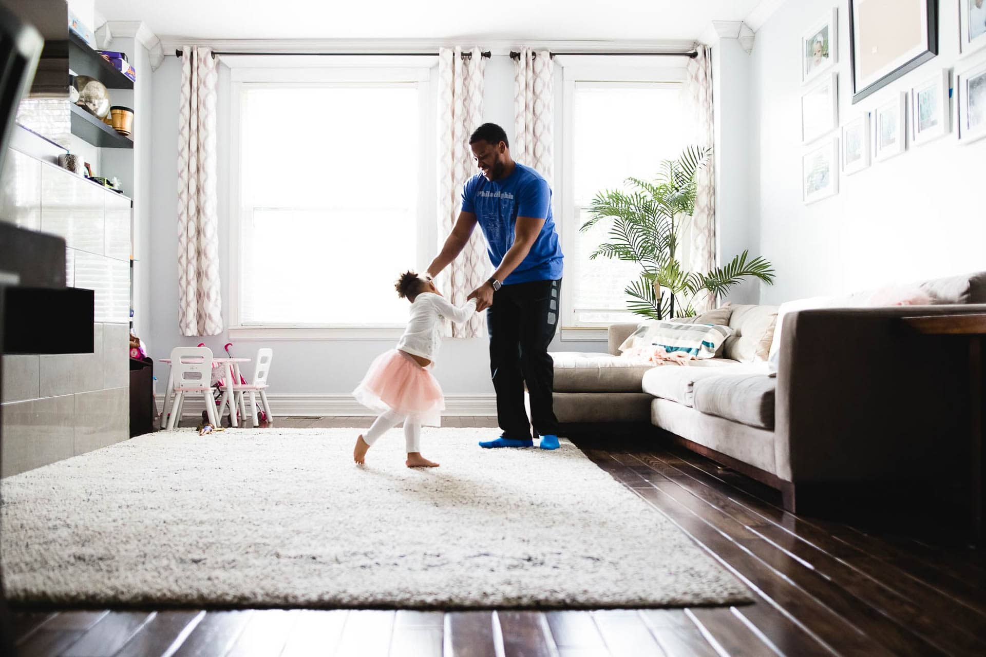 dad dances with toddler daughter in tutu in living room Old City Philadelphia Lucy Baber Photography