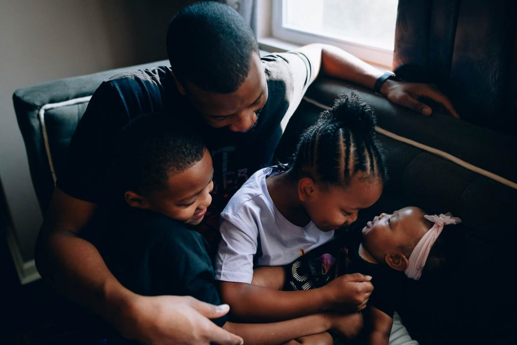 father sits on couch with three young children at home Germantown Philadelphia Lucy Baber Family Photography