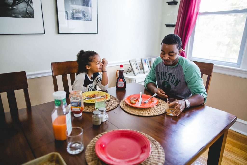 father and daughter eat breakfast together and laugh at home Old City Philadelphia Lucy Baber Family Photography