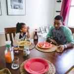 Dad eats dinner with daughter at table in home Center City Philadelphia Lucy Baber Top Family Photography