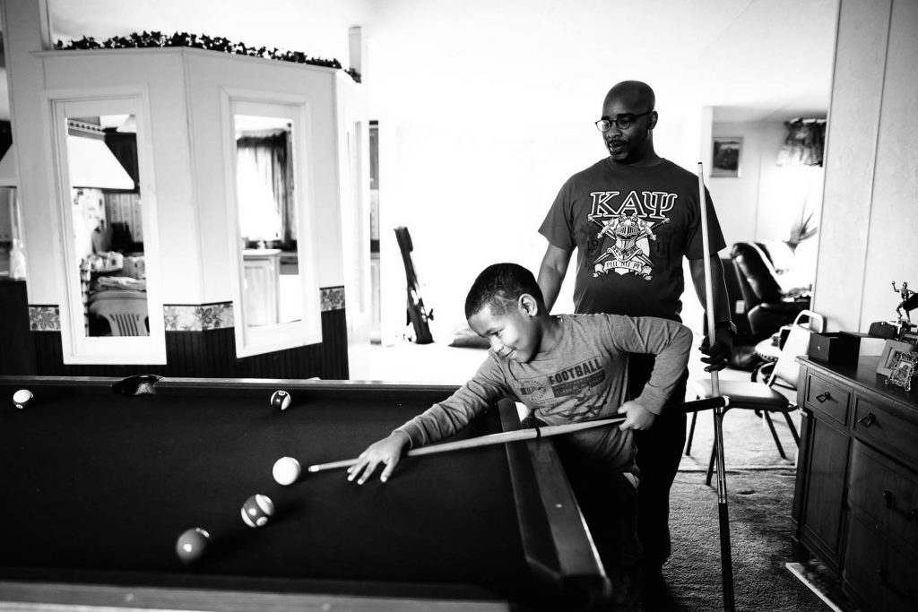 father plays pool with young son at home Chestnut Hill Philadelphia Lucy Baber Family Photography