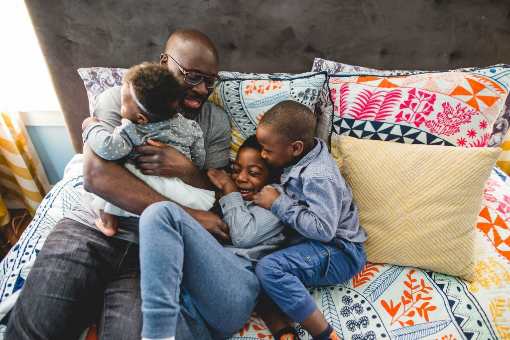 father snuggles his three kids on bed at home Mt. Airy Philadelphia Lucy Baber Family Photographer