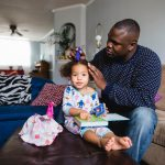 father does toddler daughter's hair as she plays in living room Ardmore PA Lucy Baber Family Photographer
