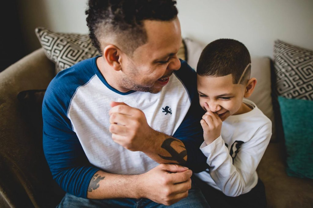 father and toddler son laugh together on the couch Bala Cynwyd PA Lucy Baber Photography