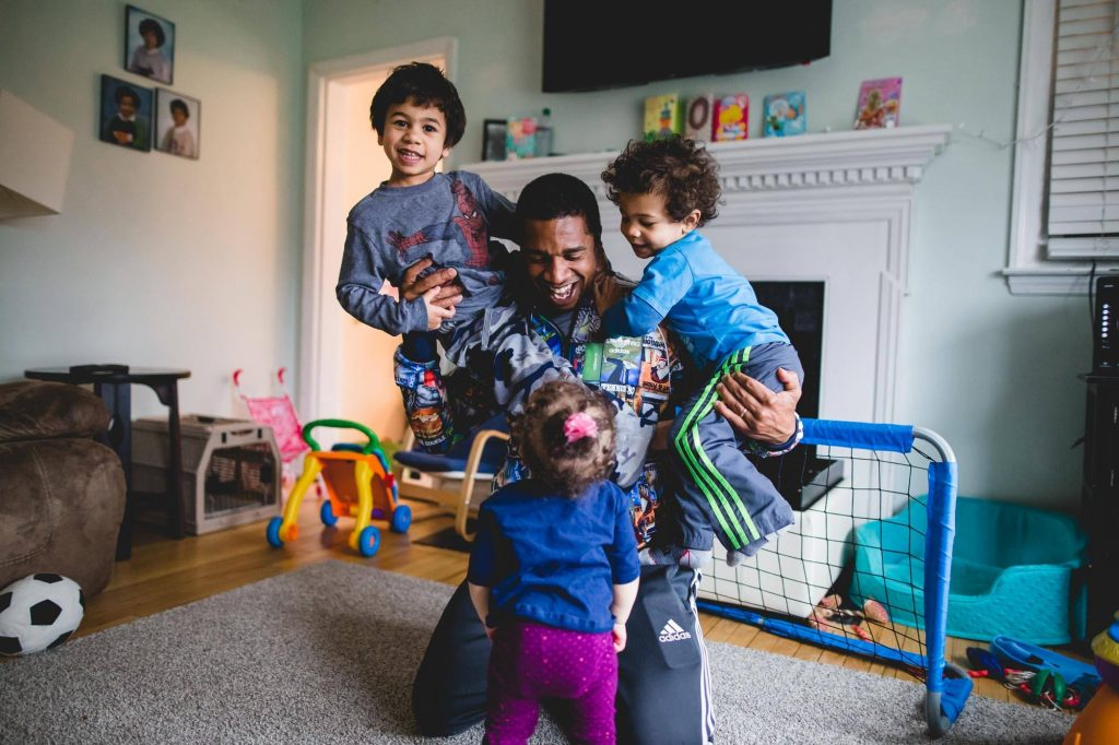 father plays soccer inside with his three young children Rosemont PA Lucy Baber Photography