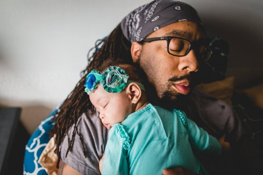 sleeping father holds sleeping newborn daughter at home Narberth PA Lucy Baber Photography