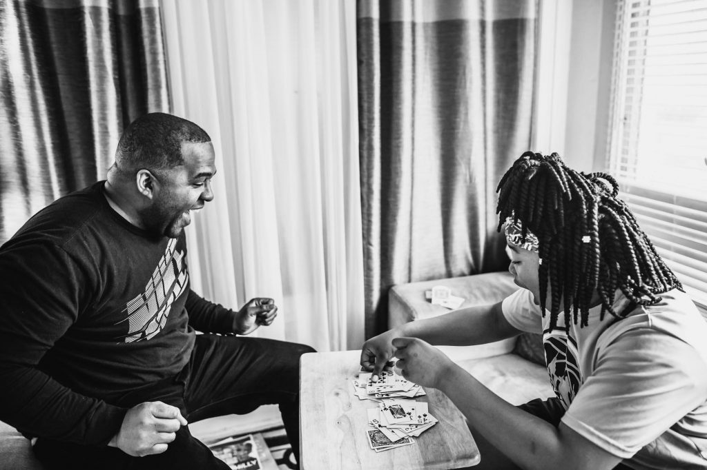 father and child laugh and play cards together at home Willow Grove PA Lucy Baber Photography