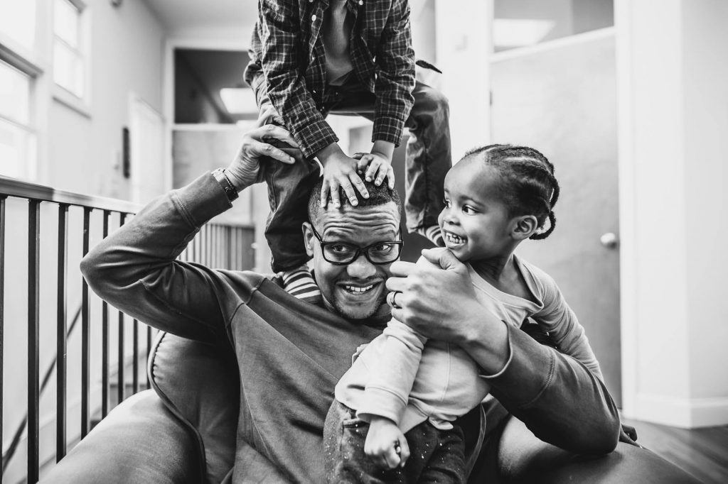 father sits in chair holding daughter and son climbing on shoulders Fort Washington PA Lucy Baber Photography