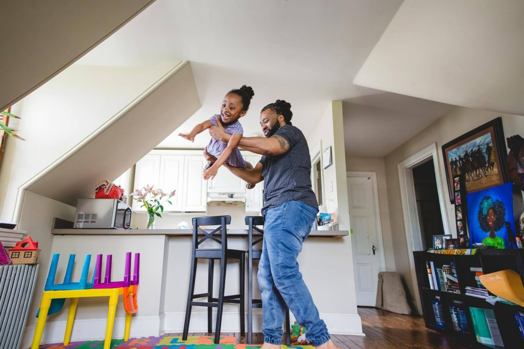 dad lifts and spins daughter like airplane in living room Glenside PA Lucy Baber Photography