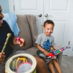 father and son play toy musical instruments together at home University City Philadelphia Lucy Baber Family Photographer
