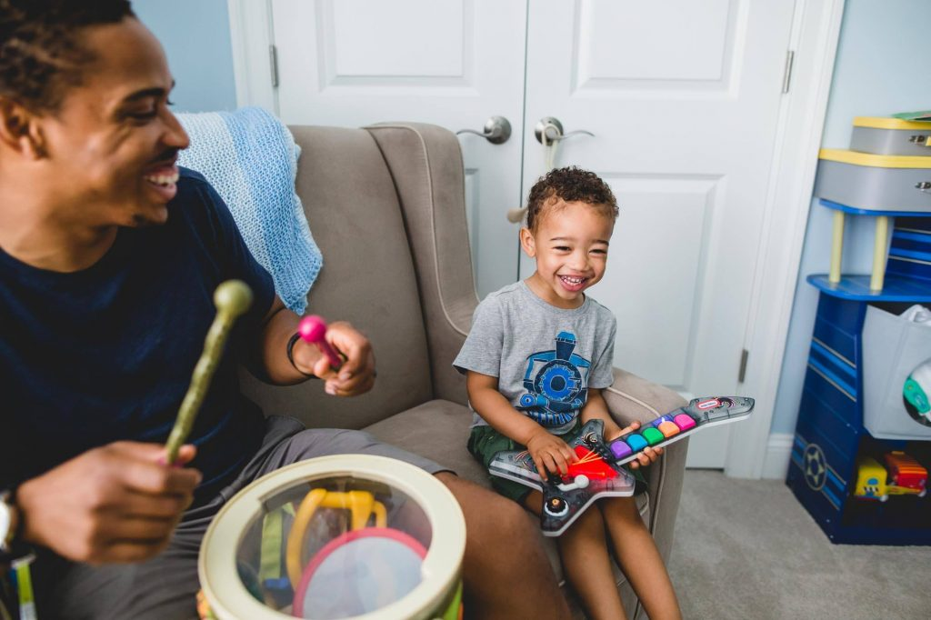 father and son play toy musical instruments at home Passyunk Philadelphia Lucy Baber Photography