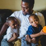 dad and two toddler sons sit together on couch at home Germantown Philadelphia Lucy Baber Family Photographer