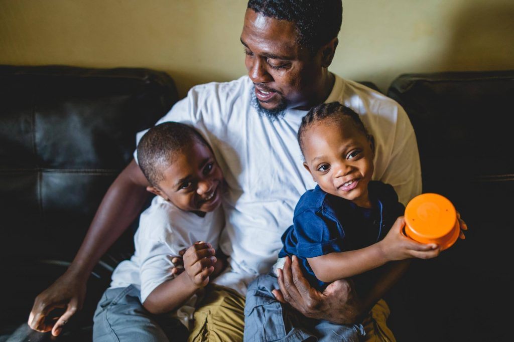 dad sits on couch holding two toddler sons Fitler Square Philadelphia Lucy Baber Photography