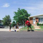 Dad and son clean up the street in front of house West Philadelphia Lucy Baber Family Photography