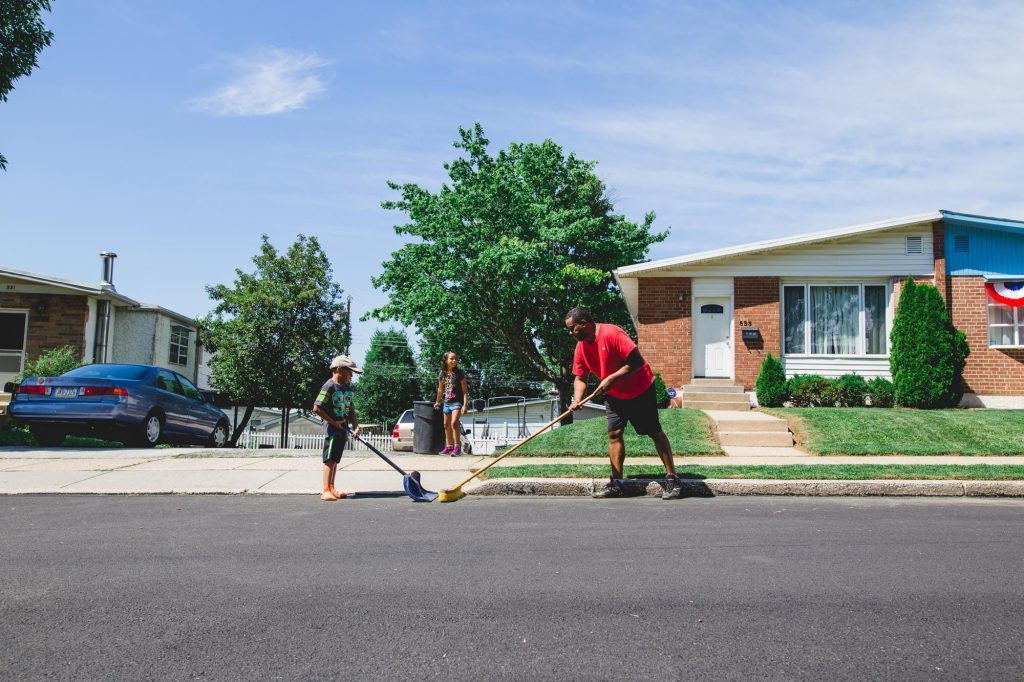 father and son clean up street in front of house Fairmount Philadelphia Lucy Baber Photography