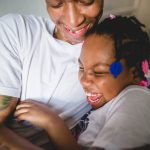 Father and young daughter hug and laugh at home South Philadelphia Lucy Baber Family Photographer