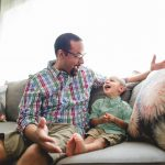 Dad and son sit on cough and laugh at home Center City Philadelphia Lucy Baber Family Photographer