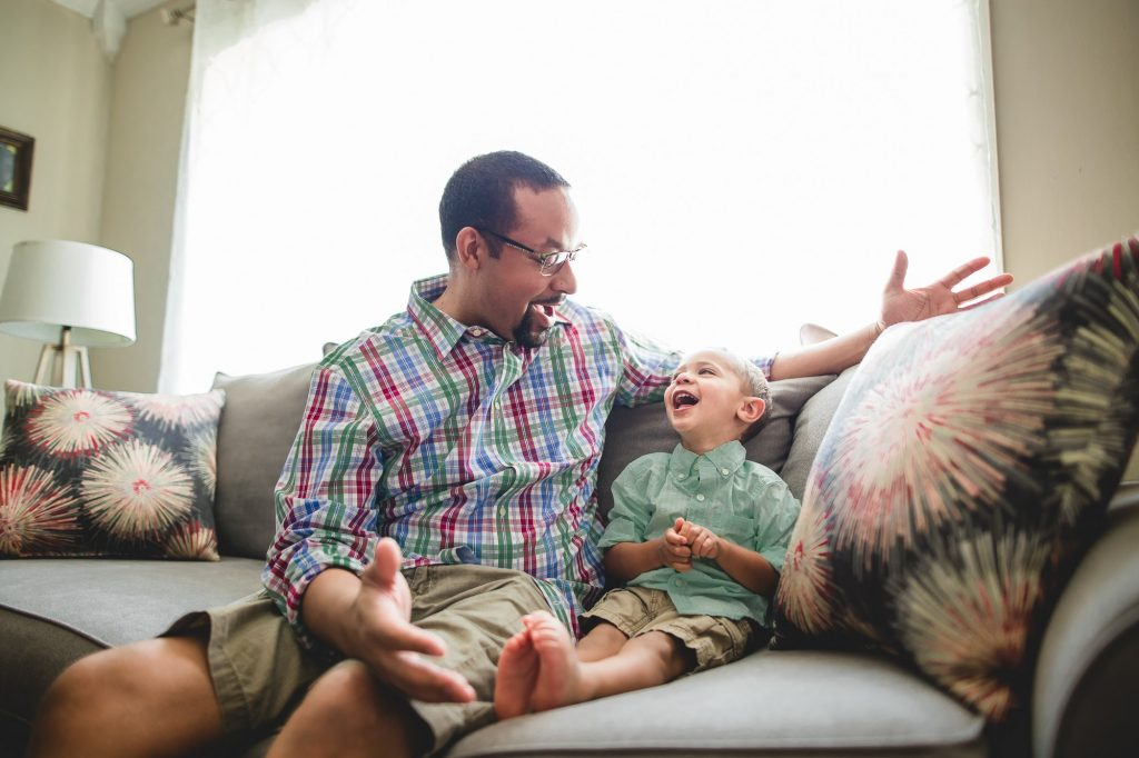dad laughs with toddler son on couch at home University City Philadelphia Lucy Baber Photography