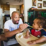 Father feeds infant child food in high chair at home Northwest Philadelphia Lucy Baber Family Photographer