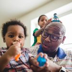 Black Dad plays two two small children at home Grey's Ferry Philadelphia Lucy Baber Family Photography