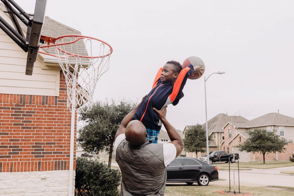 dad lifts up son to dunk a basketball in driveaway Queens Village Philadelphia Lucy Baber Photography