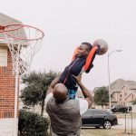 dad holds up son so he can dunk basketball South Philadelphia Lucy Baber Family Photographer