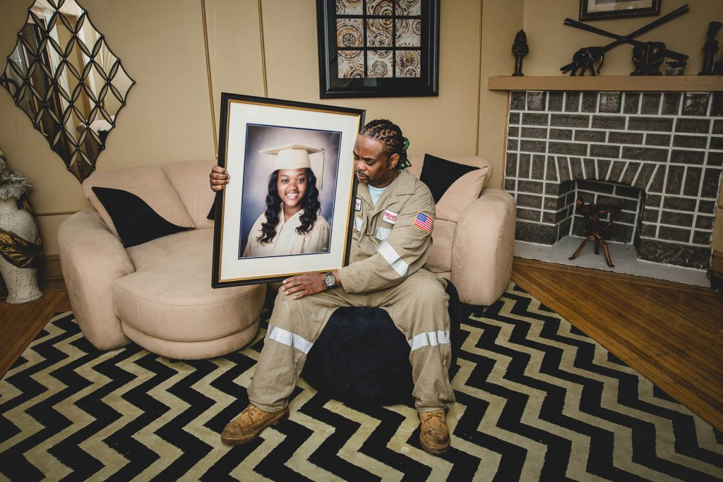 father holds framed graduation photo of his daughter who was killed Fishtown Philadelphia Lucy Baber Family Photographer