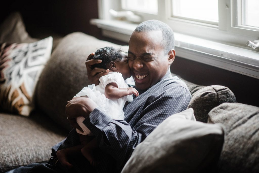 smiling father holds newborn daughter close on couch at home Chestnut Hill Philadelphia Lucy Baber Photography