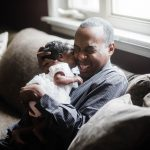 Dad smiles and holds newborn daughter close at home South Philadelphia Lucy Baber Family Photographer