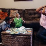 Cedric plays board game with two sons at home 100 Black Dads Lucy Baber Photography