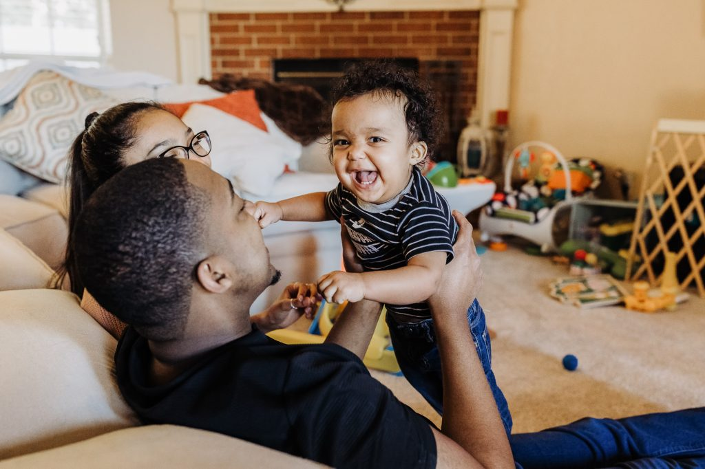 dad hold laughing infant son and plays with daughter at home Flourtown PA Lucy Baber Family Photographer