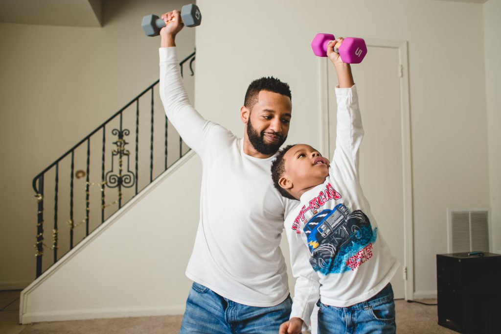 father lifting weights with his young son in living room South Philadelphia Lucy Baber Family Photographer
