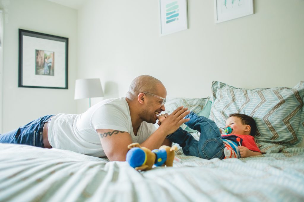 dad playing with infant son in bedroom at home Lucy Baber Philadelphia Family Photographer