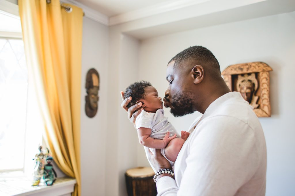 father gives his newborn baby a kiss in nursery of home Philadelphia Lucy Baber Family Photographer