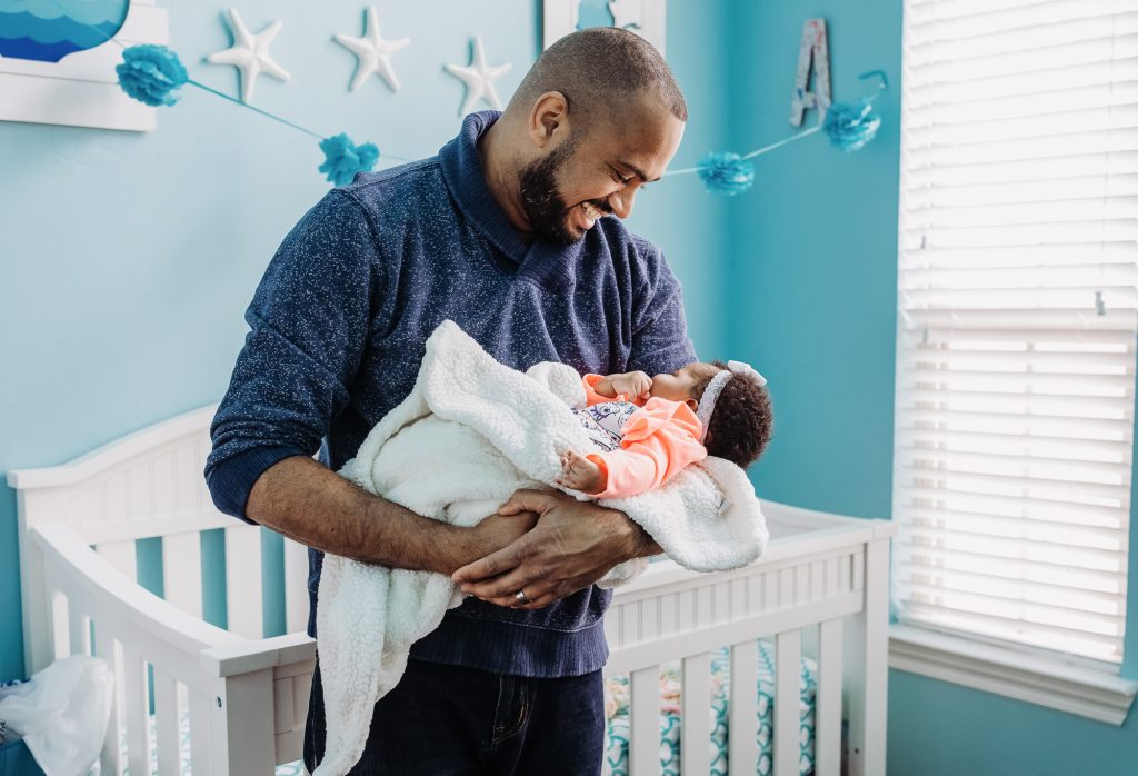 new father holding infant baby in nursery Manayunk Philadelphia Lucy Baber Family Photographer