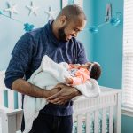 Dad holds newborn baby in nursery during home photo session Philadelphia