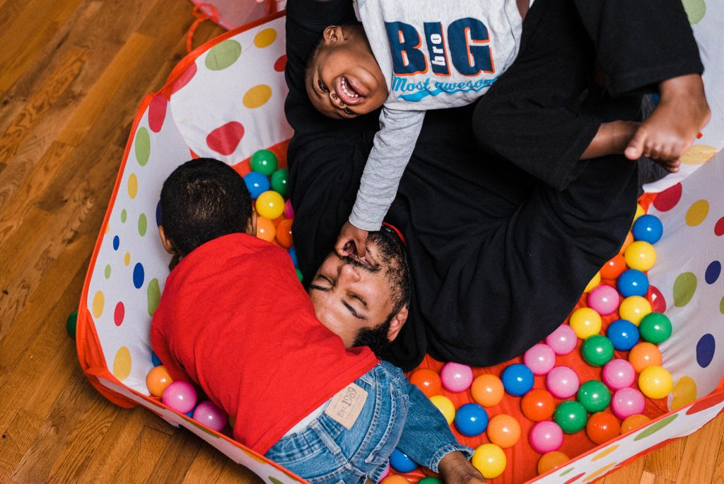 father playing in ball pit with two children at home Center City Philadelphia Lucy Baber Family Photographer