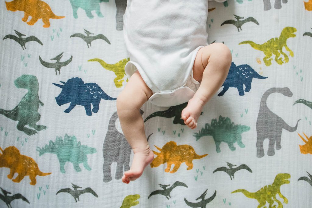 newborn baby lies on dinosaur blanket in nursery West Philadelphia Lucy Baber Family Photography