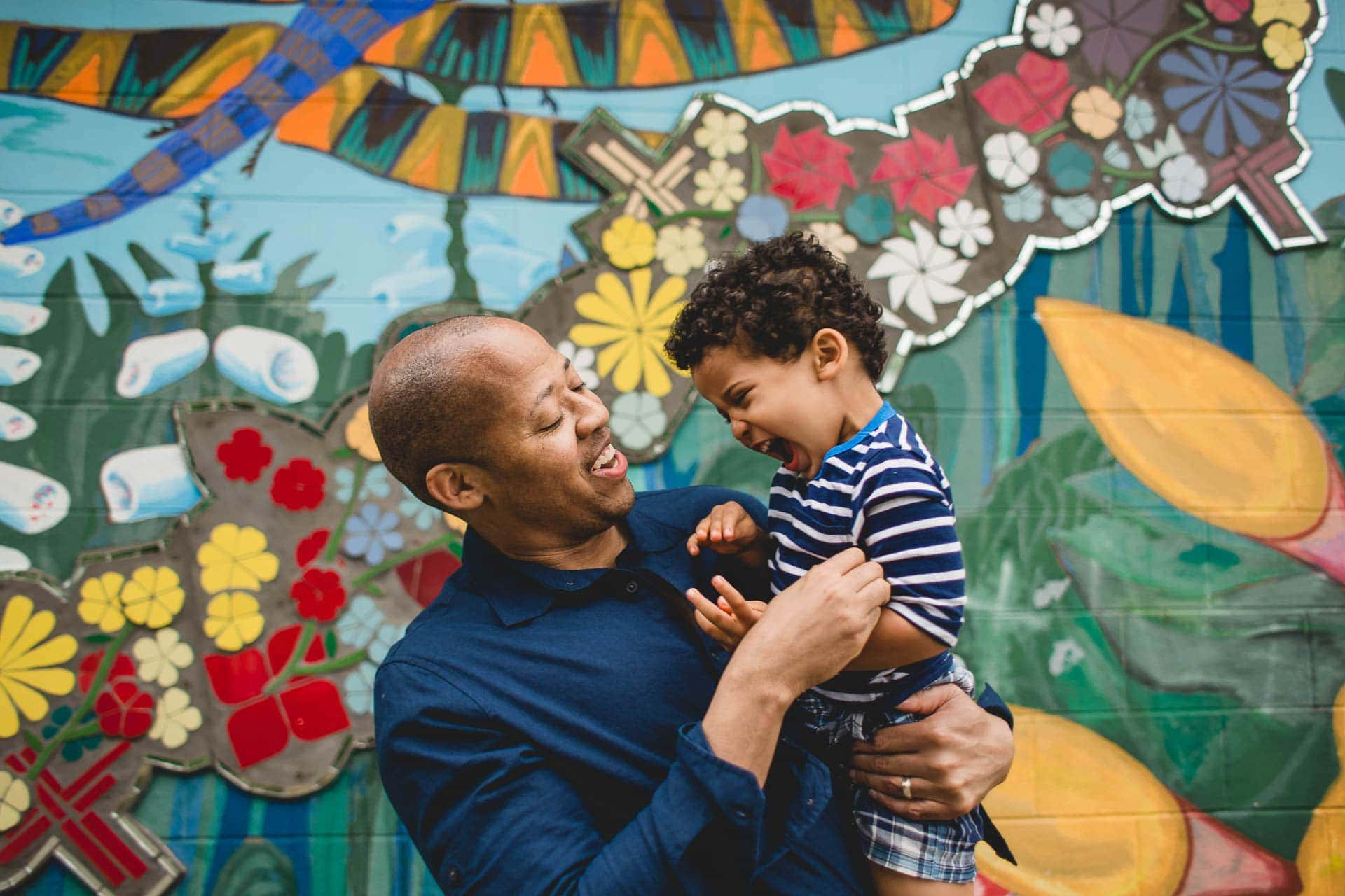 Parent laughs with toddler son in front of mural wall Philadelphia family session Lucy Baber Photography