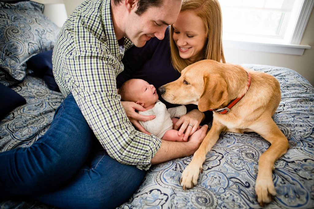 Parents introduce new baby to pet dog at home photo session Philadelphia Lucy Baber Family Photography