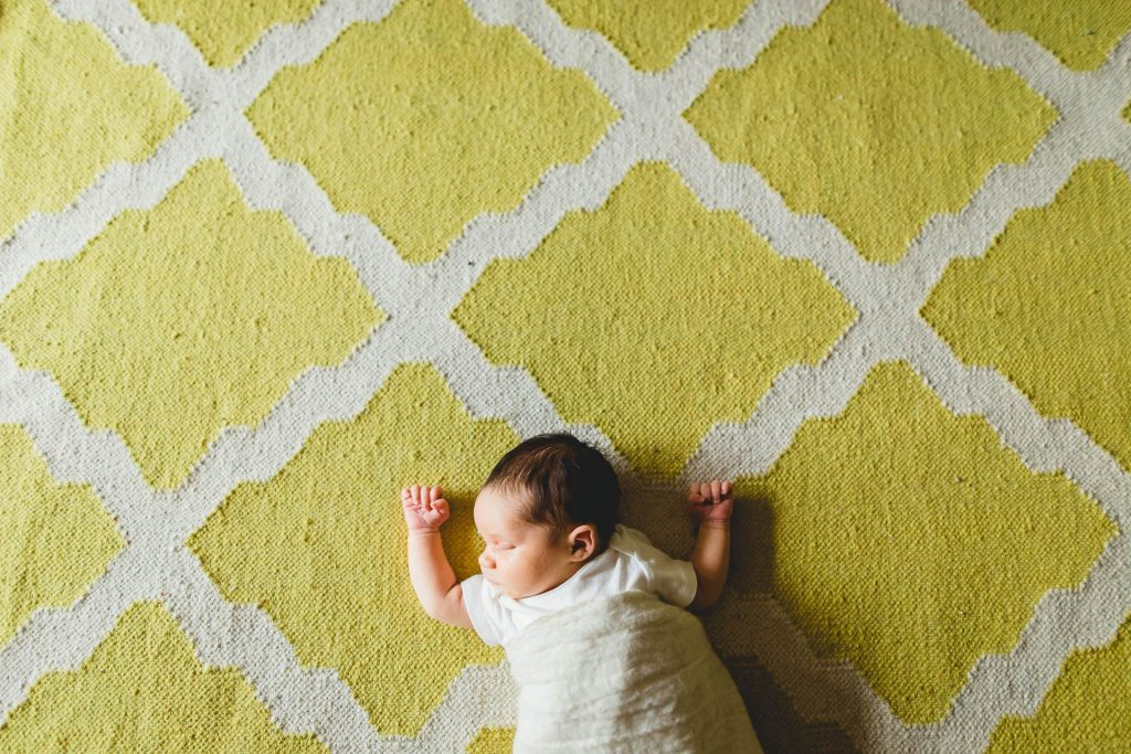 newborn baby lies on yellow carpet in nursery My. Airy Philadelphia Lucy Baber Family Photography