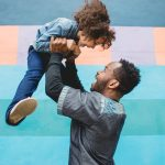 father lifts up toddler child in air in front of mural wall Philadelphia Lucy Baber Family Photographer