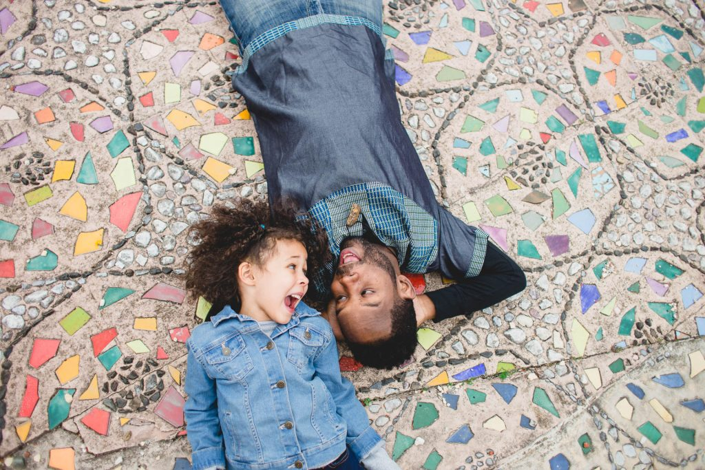 Dad and daughter lie on mosaic floor during Philadelphia park family session Lucy Baber Photography