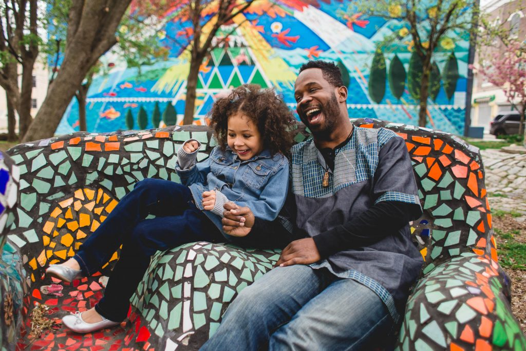 Dad and child laugh and sit on mosaic bench in front of mural wall Fairmount Philadelphia Lucy Baber Photography