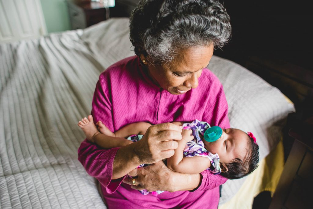 Grandmother holds newborn girl in arms at home Northern Liberties Philadelphia Lucy Baber Family Photography