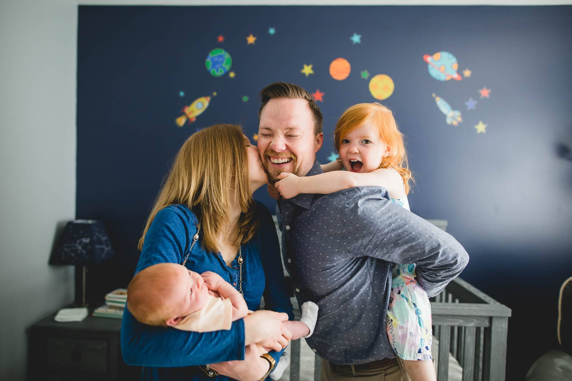 Mom and dad hold newborn baby with toddler daughter on shoulders in space themed nursery Philadelphia Lucy Baber Family Photography