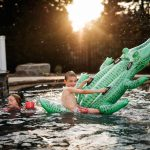 kids playing in pool on inflatable alligator during summer family photo session