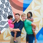 two dads hold their young kids in front of mural wall in park Fairmount Philadelphia Lucy Baber Family Photography